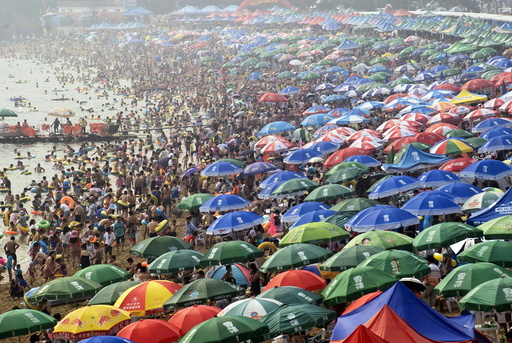 People crowd on a beach to escape the summer heat on a hazy day in Dalian, Liaoning province, China