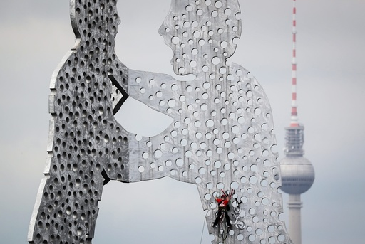 Climbing experts remove a bicycle from Molecule Man sculpture in Berlin