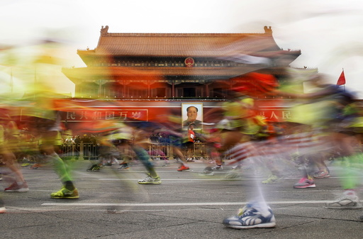 Participants run past the Tiananmen gate, with a portrait of China's late leader Mao hanging on it, during the Beijing International Marathon in Beijing