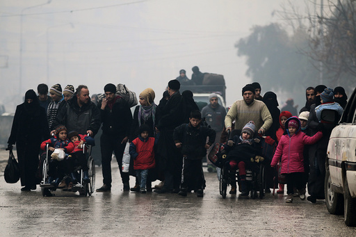 People walk as they flee deeper into the remaining rebel-held areas of Aleppo