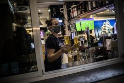 En servitør kommer med øl til bargjester i Gibraltar etter at det meste av nedstengningen på grunn av koronaviruset er opphevet. Foto: Javier Fergo / AP / NTB