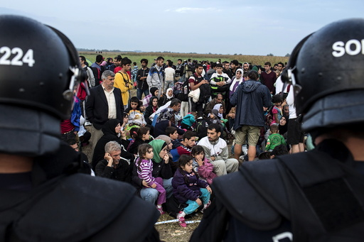 Migrants from Syria sit in front of riot police on a field after crossing into Hungary from the border with Serbia near the village of Roszke