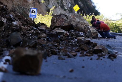 Workers try to remove a rock on the road to Illapel town after an earthquake hit areas of central Chile