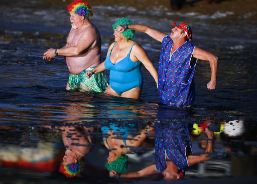Members of an ice swimming club take a dip in the lake Orankesee during the annual carnival swimming meeting in Berlin