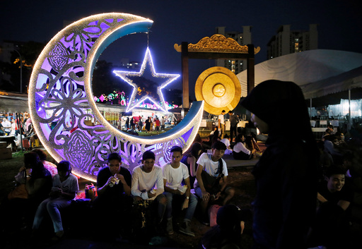 Youths break their fast at a bazaar ahead of Eid al-Fitr, which marks the end of the holy month of Ramadan, in Singapore