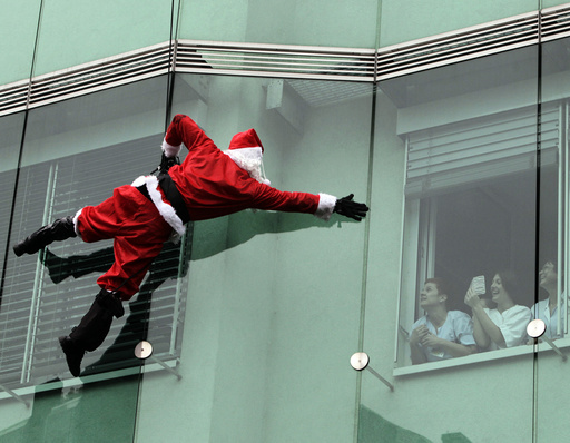 A member of the special police forces dressed in a Santa Claus suit waves to staff as he descends from the roof of a pediatrics clinic in Ljubljana