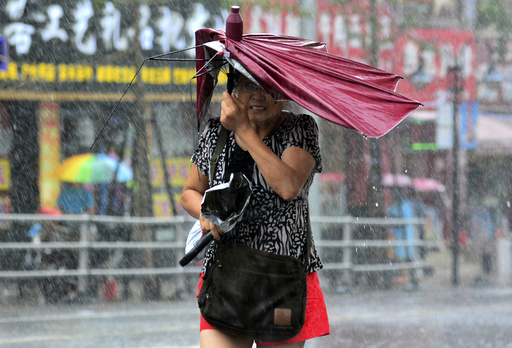 A woman holds her broken umbrella as she walks against strong wind and heavy rainfall as Typhoon Matmo hit Qingdao