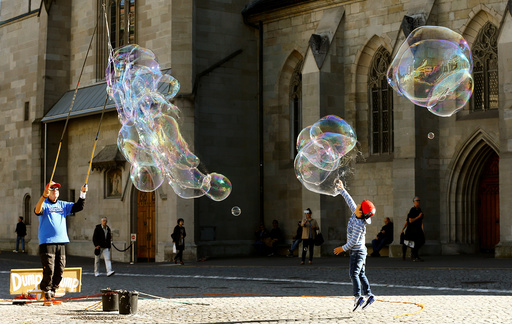 Man blows big soap bubbles during sunny autumn weather at the Muensterhof court in Zurich