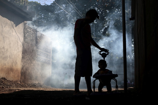 A man and his son stand outside their house while a health ministry worker fumigates in Managua