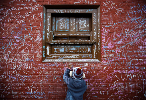 A child writes with chalk on a wall to celebrate Shreepanchami festival at Saraswati temple in Kathmandu
