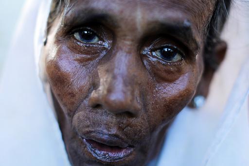 A Rohingya refugee woman rests after crossing the Myanmar-Bangladesh border in Palang Khali