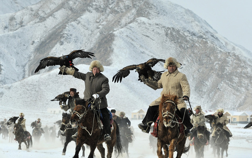 Herdsmen from the Kyrgyz ethnic group hold their falcons as they ride on horses during a hunting competition in Akqi county