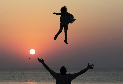 Man throws a girl into the air during sunset as they spend time on the territory of Chersonesus Tavrichesky National Reserve in Sevastopol