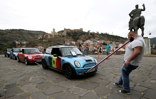 Ustiashvili pulls four cars with his teeth during an attempt to set a world record in Tbilisi