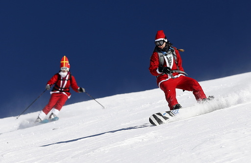 People, dressed as Santa Claus, take a curve during a promotional event on the opening weekend in the alpine ski resort of Verbier