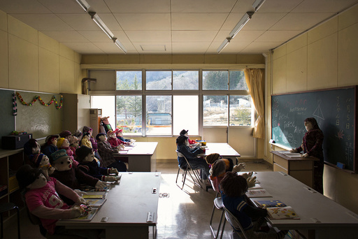 Scarecrows representing former pupils and a teacher sit in a classroom in a closed down school in the village of Nagoro
