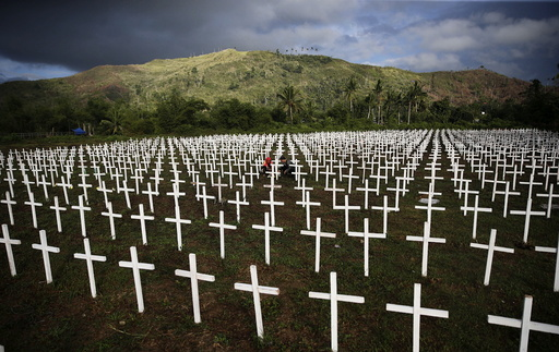 A couple visiting the graves of their four children is seen among thousands of crosses at a mass grave for Typhoon Haiyan victims on All Saints Day in Tacloban city in central Philippines