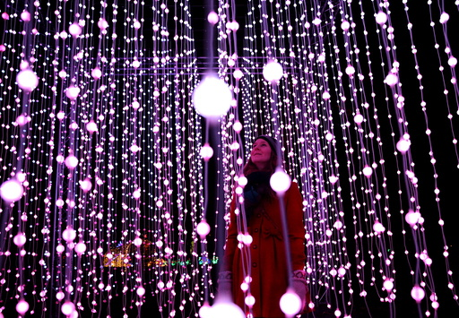 A woman poses amongst illuminations at photo-call for the Christmas at Kew Festival in London, Britain