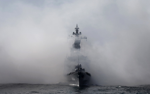 JMSDF destroyer Kurama, which is carrying Japan's PM Abe, sails in smoke during its fleet review at Sagami Bay, off Yokosuka