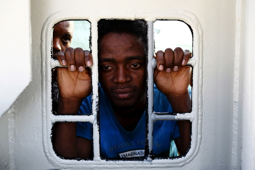 Migrants look out of a window on the Medecins Sans Frontiere (MSF) rescue ship Bourbon Argos as it arrives in Trapani, on the island of Sicily