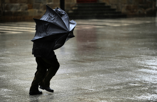A man tries to hold his umbrella in the midst of strong gusts of wind in Gijon
