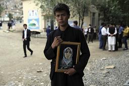 En ung mann holder er bilde av sin søster som ble drept i et bombeangrep på en jenteskole i Kabul 8. mai, der rundt 90 mennesker ble drept, de fleste unge skolejenter. Foto: Rahmat Gul / AP / NTB