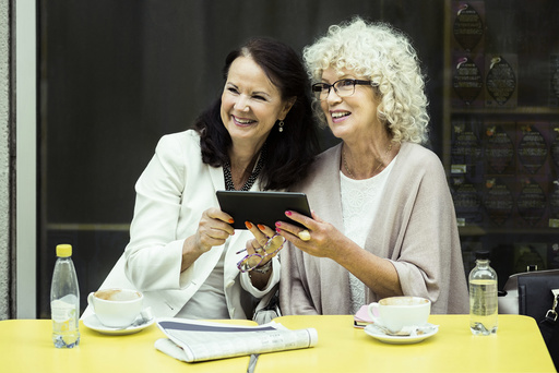 Happy senior women with digital tablet looking away at outdoor cafe