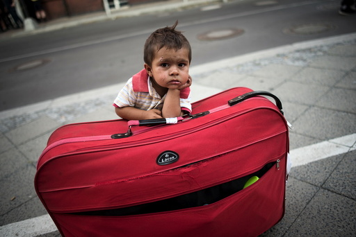 Migrant boy waits at his parents' suitcase as they leave the Berlin State Office for Health and Social Affairs with other newly arrived refugees who waited all day to apply for asylum in Berlin