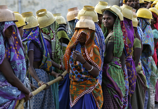 Female labourers wearing helmets take a break from laying underground electricity cables in Ahmedabad