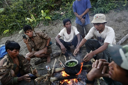 Naga men prepare dinner at a hunting base camp in an opium field during a hunting trip between Donhe and Lahe township in the Naga Self-Administered Zone