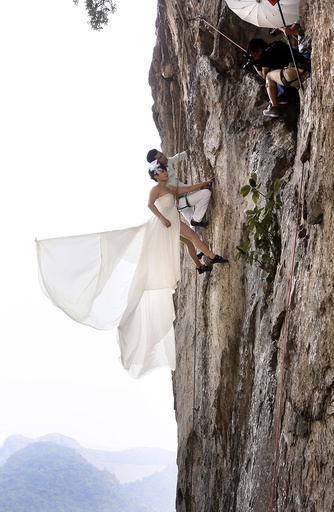 Fang Jing in a wedding gown and her husband, surnamed Zhao, pose for photographs as they hang from a cliff during a rock climbing exercise in Liuzhou