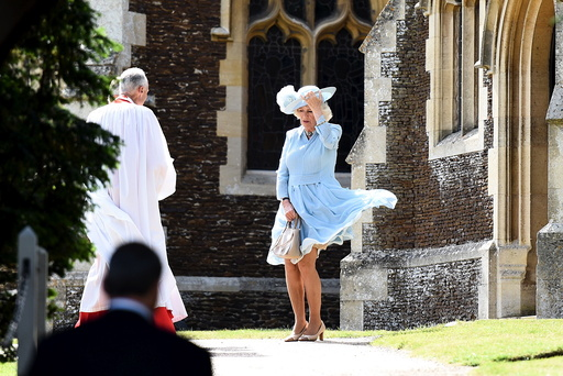 Camilla, the Duchess of Cornwall, controls her skirts as a gust of wind blows while she arrives at the Church of St Mary Magdalene on the Sandringham Estate for the christening of Princess Charlotte