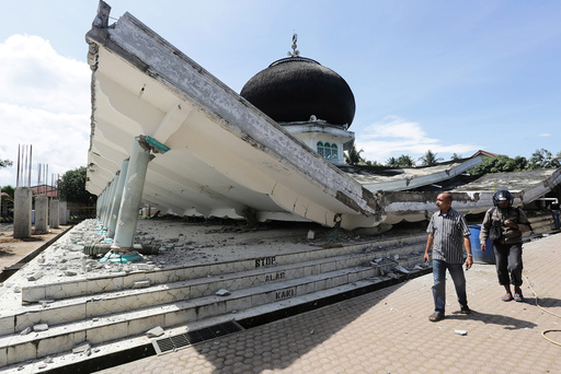 People walk near a collapsed mosque following an earthquake in Meuredu, Pidie Jaya in the northern province of Aceh