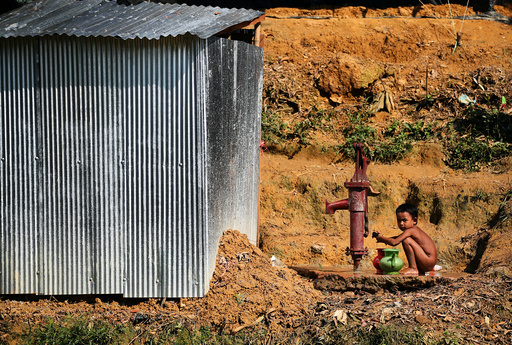 A Rohingya refugee boy fetches water from a water pump in Kutupalong refugee camp near Cox's Bazar