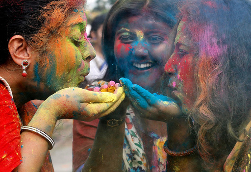 Students of Rabindra Bharati University blow colour powder during Holi, the Festival of Colours, celebrations inside the university campus in Kolkata