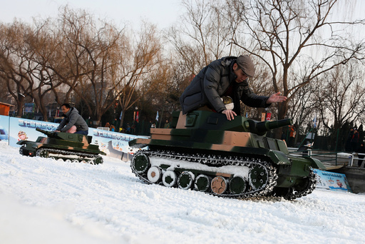 People ride in electric toy tanks in Taoranting park in Beijing