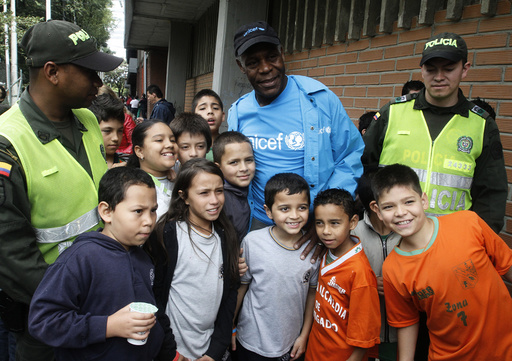 UNICEF Goodwill Ambassador and actor Glover poses with children after his arrival at a soccer stadium in Envigado