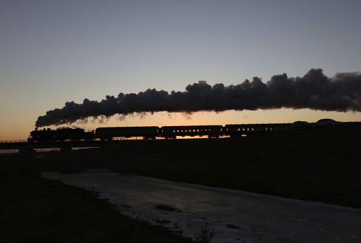 A steam train travels among crop fields at the annual steam train festival during sunrise in Diaobingshan