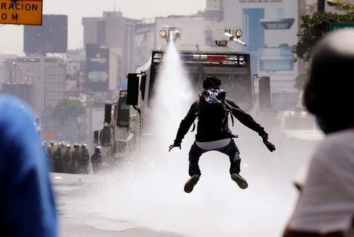 A demonstrator jumps away from a jet of water released from a riot security forces vehicle during a rally against Venezuela's President Nicolas Maduro in Caracas