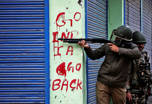 An Indian policeman aims his gun during an anti-India protest in Srinagar