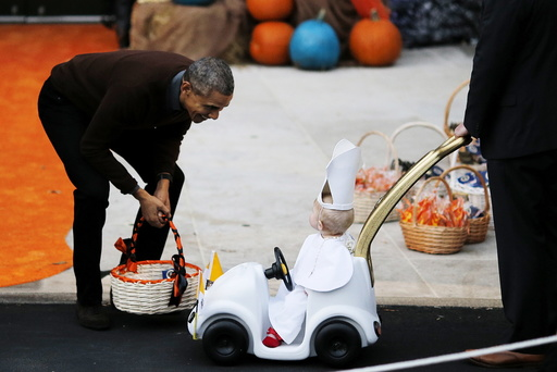 U.S. President Barack Obama receives a child dress as the Pope Francis on the South Lawn of the White House during a Halloween trick-or-treating celebration in Washington