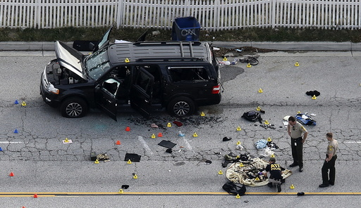 Law enforcement officers look over the evidence near the remains of a SUV involved in the Wednesdays attack is shown in San Bernardino, California