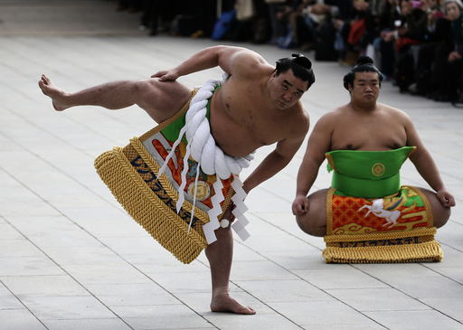 Mongolian-born grand sumo champion Yokozuna Harumafuji performs the New Year's ring-entering rite at the annual celebration for the New Year at Meiji Shrine in Tokyo