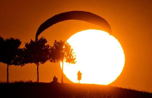 A Paraglider lands at sunset