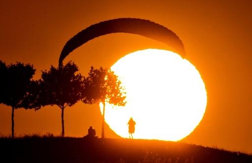 A Paraglider lands at sunset