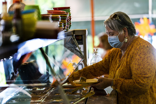 Gloria Arrellano, 68, wears a face mask as she serves herself a plate at Taqueria El Sol buffet in Los Angeles' Boyle Heights neighborhood in Los Angeles, Thursday, July 22, 2021. The restaurant requires all his customers to wear face masks while standing in the buffet area of the Mexican restaurant. (AP Photo/Damian Dovarganes)