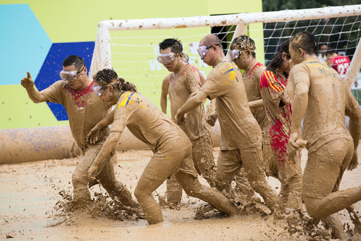 People play during their match at a swamp soccer tournament in Beijing, China