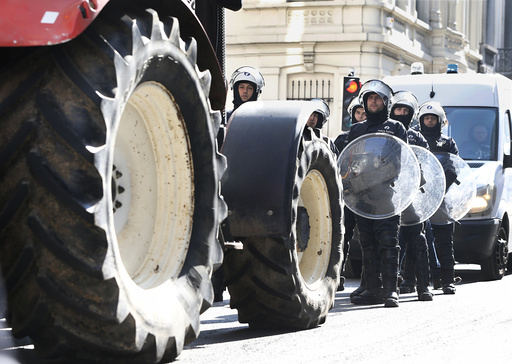 Riot police face off with farmers during a demonstration near the EU headquarters Brussels