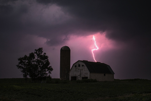 Lighting strikes over a barn surrounded by a soybean crop in Donnellson, Iowa
