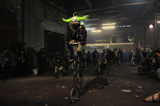 People ride bicycles in Halloween costumes during